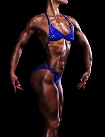 muscled: Slim muscled woman against black background  Stock Photo