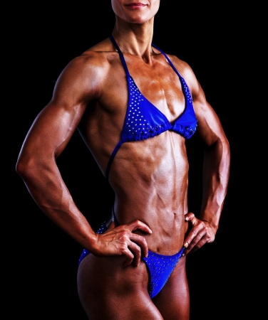 Slim muscled woman against black background photo