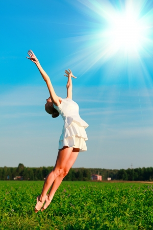 Woman jumps in a green field  photo
