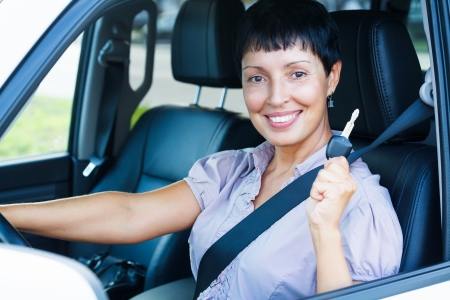 Senior woman holding car key and smiling to you from a car  photo