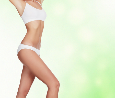Slim woman against an abstract green