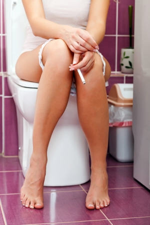 Smoking woman in the toilet Stock Photo - 22817139
