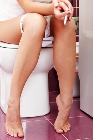 Smoking woman in the toilet Stock Photo - 22885899