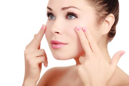 Vrouw masseert haar gezicht met haar vingers, witte achtergrond Stockfoto