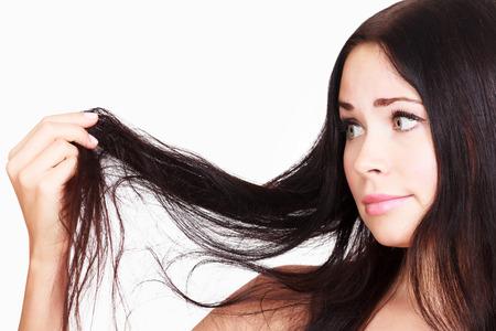 ブルネットの女性が彼女の壊れやすい髪、白い背景、copyspace に満足していません。 写真素材