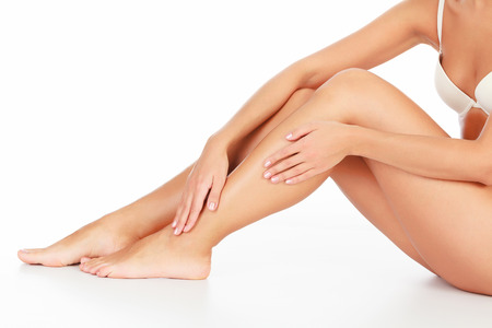 Woman touches her leg, white background, copyspace photo