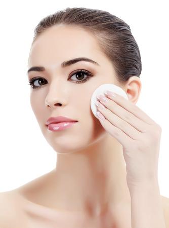 美しい女性の綿のパッドを使用して彼女の化粧を削除します。Copyspace 白い背景で隔離