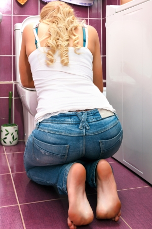 bulimia: Hangover after party, woman in the toilet Stock Photo