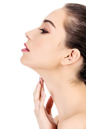Hermosa chica con piel limpia y fresca toca su cuello, fondo blanco