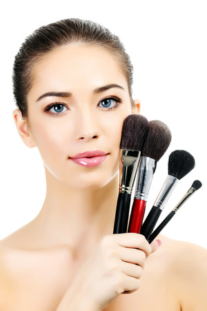 Pretty woman with cosmetic brushes, white background  photo