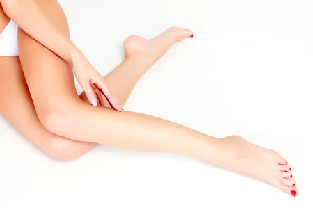 Woman sits on the floor and touches leg by hand  photo