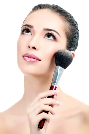 make up brush: Pretty woman with a cosmetic brush, white background