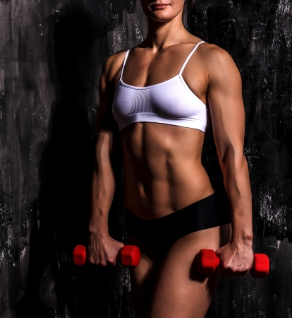 Muscled woman with barbells Stock Photo