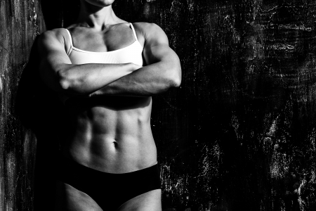 muscled: Muscled woman against the scratched grunge  Stock Photo