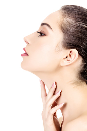 Young female touches her neck, white background, copyspace 免版税图像