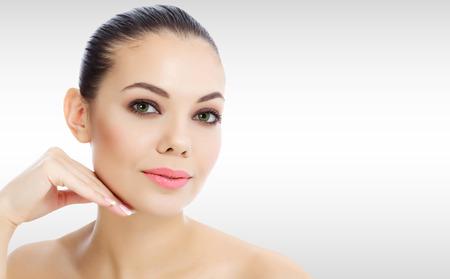 Mooie vrouw tegen een grijze achtergrond met copyspace Stockfoto