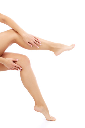 varicose veins: Female hands and legs on white , copyspace Stock Photo