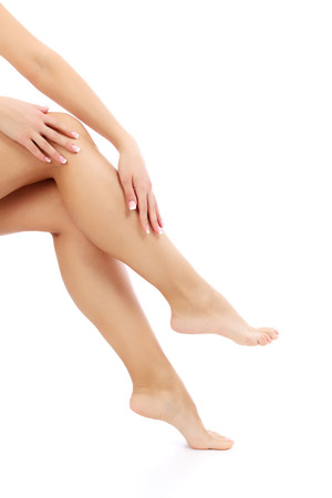 varicose veins: Female hands and legs on white , copyspace