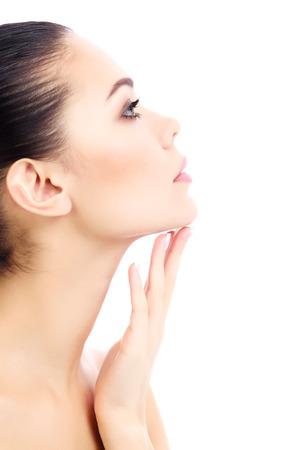 Jeune femme touche son cou, fond blanc, copyspace