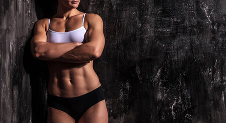 muscled: Muscled woman against a grunge background Stock Photo