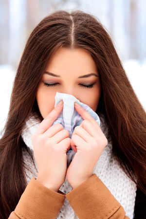 woman with a cold holding a tissue, outdoors Stock Photo - 26551443