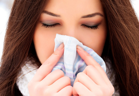 blowing nose: woman with a cold holding a tissue, outdoors