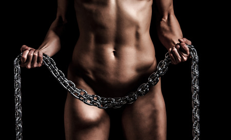 Strong woman with a metal chain, black background Stock Photo