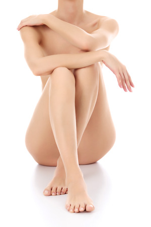 Slim woman sitting on a white floor, white background.