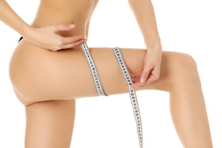 cintas metricas: La mujer mide su muslo, fondo blanco, copyspace