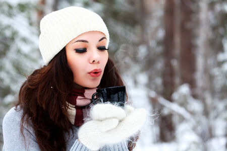 Beautiful young woman in knitted hat and sweater blows on hot tea or coffee