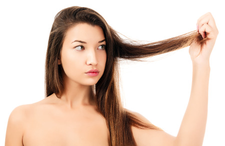 frizzy: woman is not happy with her fragile hair, white background, copyspace