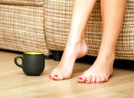 Female feet and a cup of tea or coffee photo