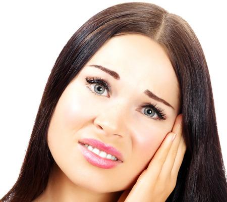 dolor de oido: Mujer joven con un dolor en el oído, fondo blanco, copyspace