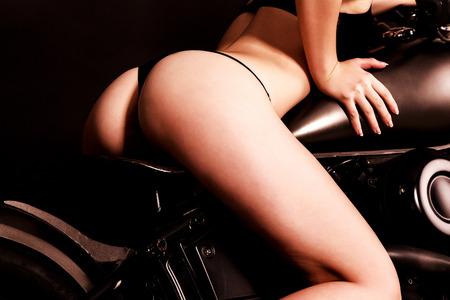 Sexy woman on a black bike Stock Photo