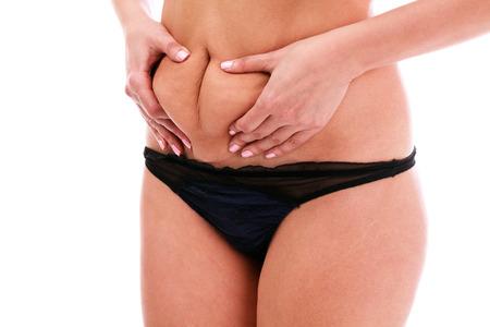 mujeres gordas: Mujer aprieta la grasa en su vientre, aislado, fondo blanco