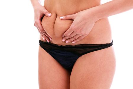 Woman pinches fat on her belly, isolated, white background