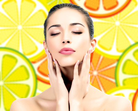 touching face: Good looking female on a background with orange slices