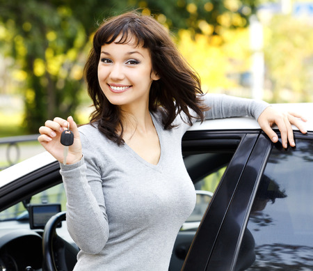busty: Muchacha bonita que muestra la llave del coche Foto de archivo