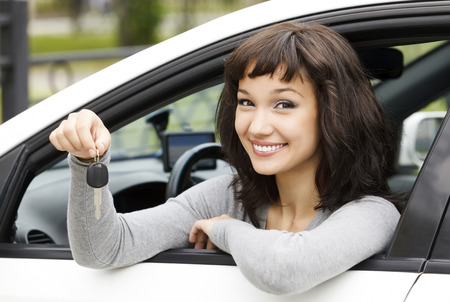 Pretty female driver in a white car showing the car key 스톡 콘텐츠