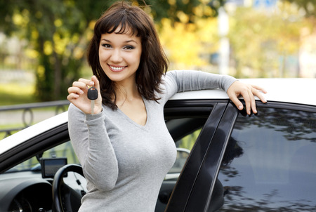 auto leasing: Pretty girl in a car showing the key.