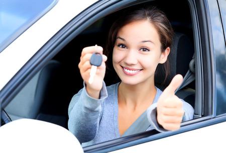 Gelukkig meisje in een auto met een sleutel en duim omhoog gebaar