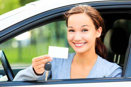 drivers: Happy girl in a car showing a key and an empty white card for your message.