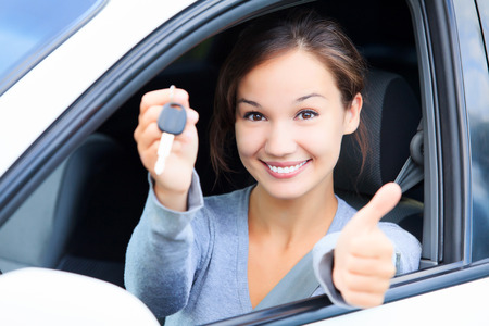 Happy girl in a car showing a key and thumb up gesture photo