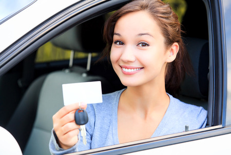 Happy girl in a car showing a key and an empty white card for your message Foto de archivo