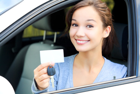 Happy girl in a car showing a key and an empty white card for your message Stockfoto