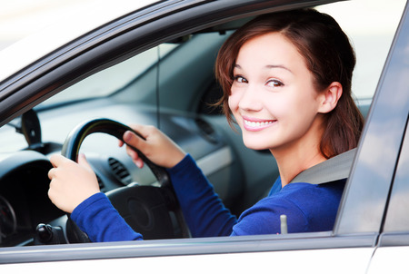 Happy female driver smiling to you Standard-Bild