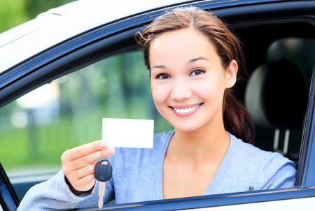 drivers: Happy girl in a car showing a key and an empty white card for your message Stock Photo
