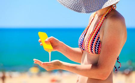 Frau, die Schutz Lotion vor Sonnenbaden am Strand Standard-Bild
