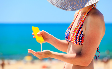 sun protection: woman applying protective lotion before sunbathing at beach Stock Photo