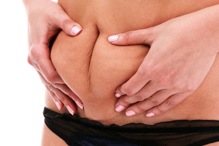 pinch: Woman pinches fat on her belly, isolated, white background